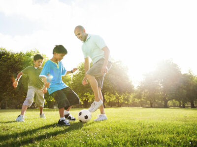 father kicks soccer ball with two sons