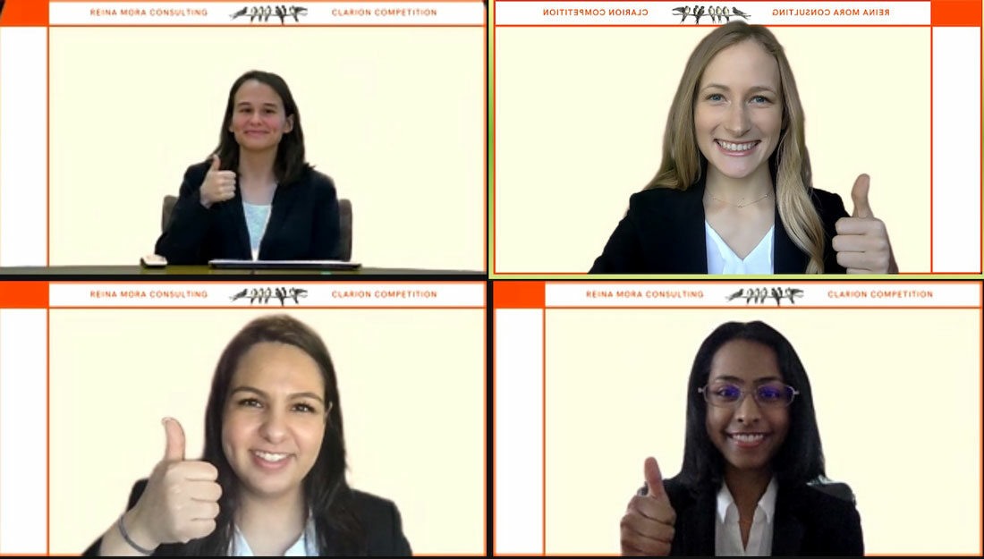 """screenshot of a Zoom call with four students giving a """"gig 'em"""" sign"""