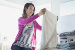 woman folds clean towels