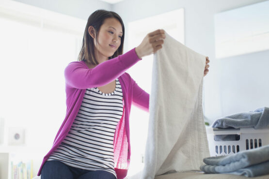 woman folds clean towels