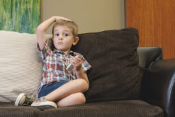 child on couch playing with cell phone