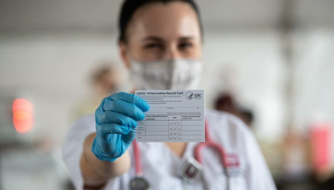 nursing student holds up a vaccination record card