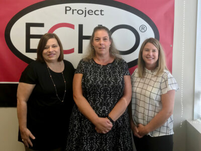 Kim Cassens, Bree Watzak, and Melissa Lackey stand in front of Project ECHO poster