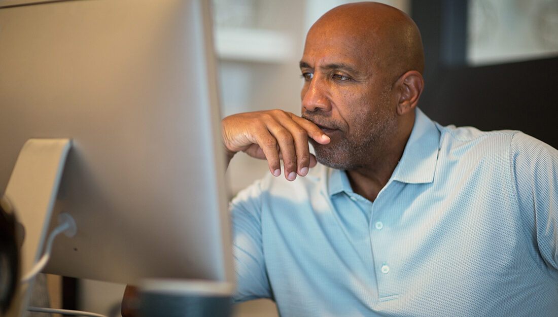 African American man holding hands in front of face while looking at computer.